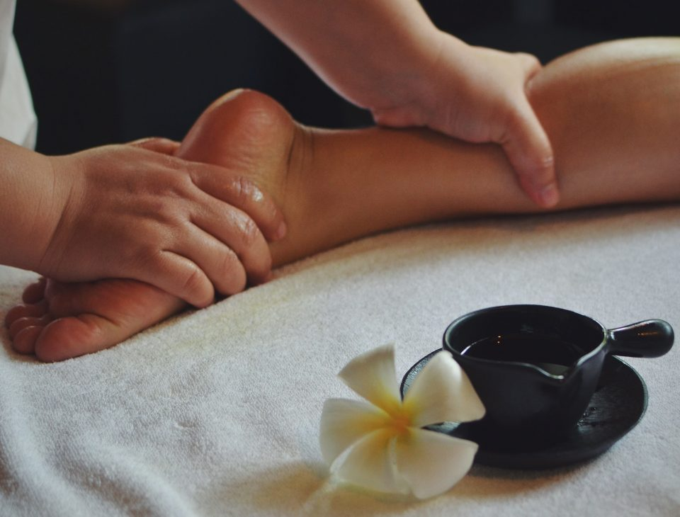 The therapist doing foot massage in spa treatment room
